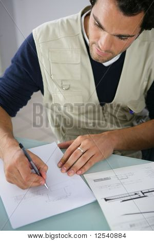 Portrait of a young man writing on a document