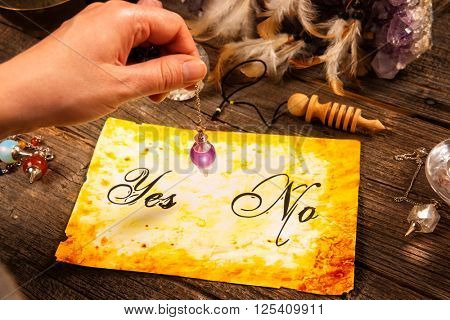 Pendulum, tool for dowsing in hand, over yes and no choosing diagram poster