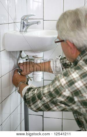 A man undoing the siphon of a washbasin