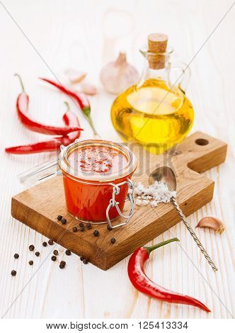 Jar of piquant sauce made from chili peppers and garlic on white wooden background