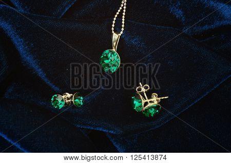 Feminine accessories: emerald pendant and earrings on velvet