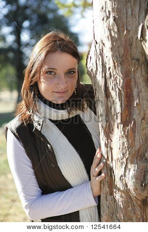Portrait of a young woman hidden behind a tree