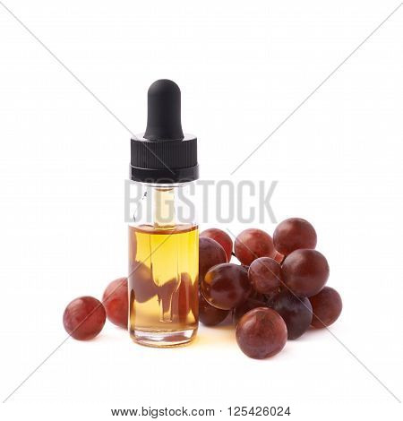 Grape seed oil essence in a small bottle with a pipette, surrounded with the multiple dark grapes, composition isolated over the white background