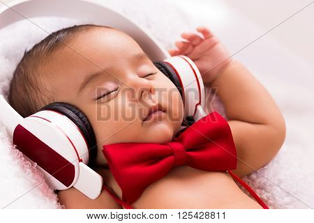 beautiful baby two months old relaxed listening music with headphones using a vintage red tie and beige pants