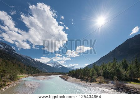 sun and clouds over flowing river at austrian mountains