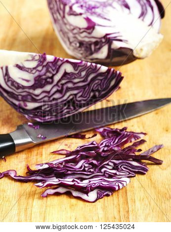 Sliced of red cabbage on wooden cooking board