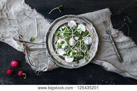 Spring salad with sunflower sprouts and radish in vintage metal plate over rustic dark painted background, top view