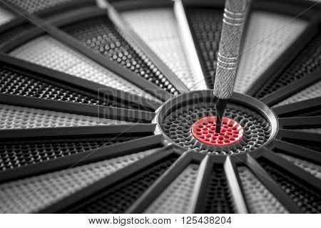 Closeup of a dart in the red center of black and grey dartboard. Selective color of the dart center in a greyscale image.