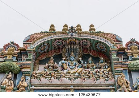 Trichy India - October 15 2013: Closeup of a statue scenery at Ranganathar Temple showing Lord Vishnu and his harem: Lakshmi to his right and Devi Bhu and Neela. Shesha the snake makes a throne for the group.