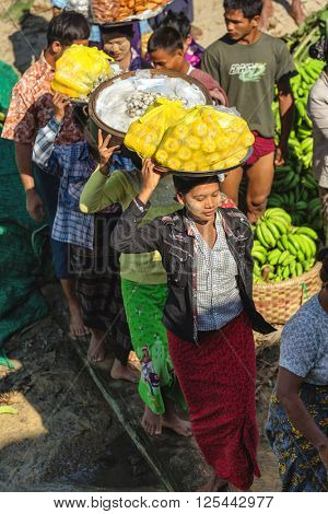 MANDALAY, MYANMAR, JANUARY 21, 2015 : Burmese women are boarding a boat by walking on a wooden plank, carrying vegetables on their heads  in Mandalay, Myanmar (Burma)