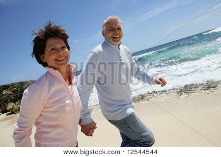 Portrait of a senior couple running on the beach
