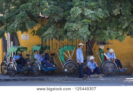 HOI AN, VIETNAM - SEPTEMBER 5, 2015: unidentified cyclo drivers of Hoi An are taking a rest and are waiting for the next trip in Hoi An,Vietnam