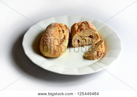 two pieces of multigrain bread roll on white plate on white table.