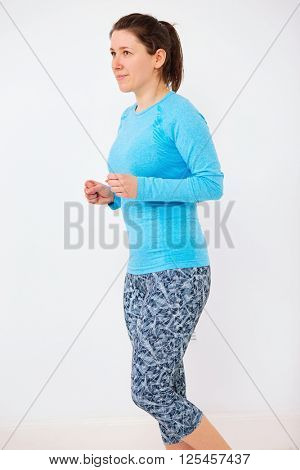 Young woman in blue top during some fitness, shoot against white wall