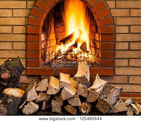 pile of firewood and fire in indoor brick fireplace in country cottage poster