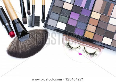 selective focus on natural smoky and dark purple eyeshadows palette and other cometics kit