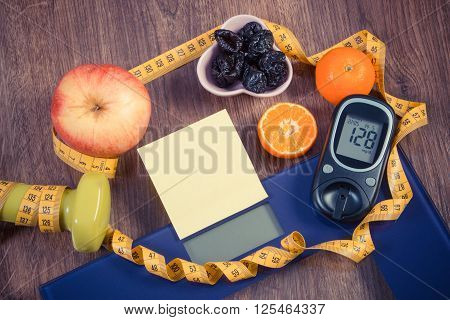 Electronic bathroom scale and glucose meter with result of measurement sugar level concept of healthy lifestyles diabetes and slimming sheet of paper for text