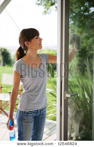 Woman cleaning the outside windows of a house