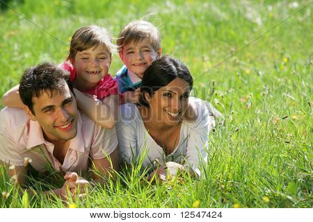 Portrait of a smiling family lying on the grass