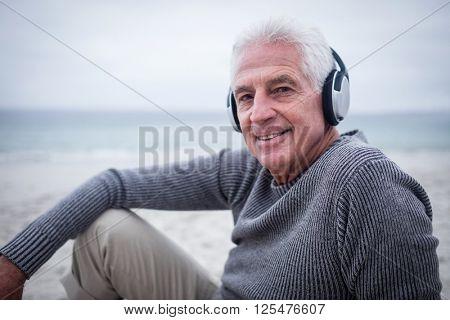 Portrait of senior man listening to music on headphone at beach
