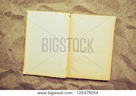 Open old vintage book with blank yellow pages as copy space flat laid in warm beach sand top view.