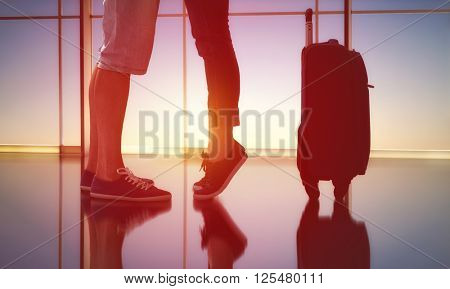 woman standing on tiptoe beside her man. the embrace of men and women in the airport. the concept of farewells and meetings.