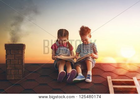 Children reading a book sitting on the roof of the house. Boy and girl reading by the light of sunset.