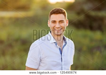 Portait of a young smile man. Close up of a gorgeous guy, outdoors