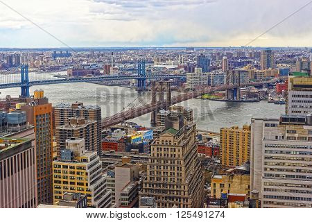 Aerial view of Lower Manhattan in New York USA Brooklyn Bridge and Manhattan Bridge over East River. Brooklyn Heights on the background.