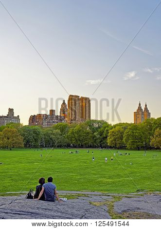 Couple looking at Uptown Manhattan skyline in Central Park West. On Upper West Side in New York USA. People nearby