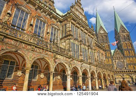 BREMEN GERMANY - MAY 1 2013: Bremen City Hall and Cathedral in Bremen in Germany. They are placed in the Market Square in the city center of Bremen. The Cathedral is also called St Peter Cathedral. People nearby