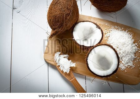 Whole and broken coconut with grated coconut flakes and coconut oil or butter.