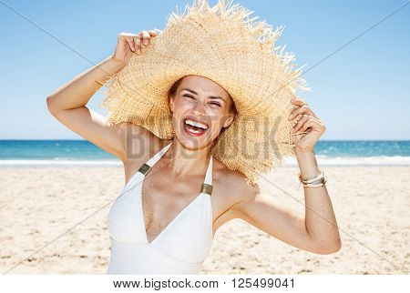 Smiling Woman In Swimsuit Playing With Big Straw Hat At Beach