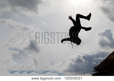 Teenage boy doing a back flip silhouetted