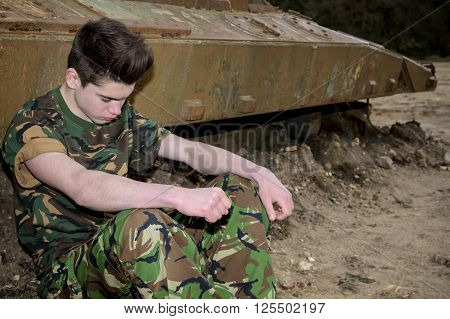 Teenage cadet soldier resting by a ruined tank