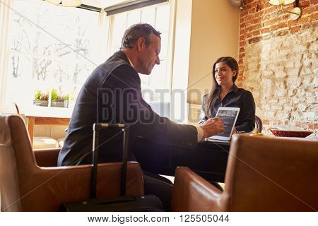 Guest checking in at hotel reception using tablet computer