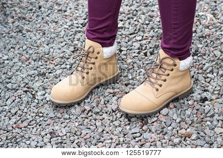 female feet shod in brown shoes standing on gravel road