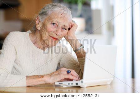 Ältere Frau, die zu Hause mit Computer eingeben