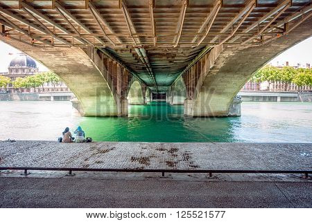 Two Women Sitting Under The Bridge Near River