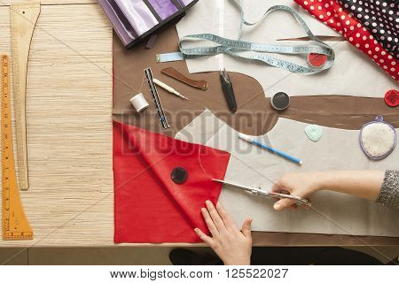 Desk designer fashion. Fashion designer starts cutting fabric to create fashionable clothes.