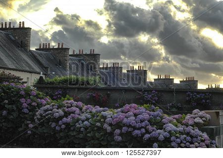 Cloudscape in Avranches (Manche Normandy France) in a summer evening. Chimneys and flowers