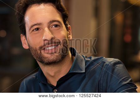Portrait of a handsome young man smiling and looking awey. Young man thinking in a evening. Smiling young man thinking about his bright future. Vision and future concept.