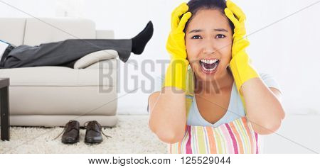 Distressed woman wearing apron and rubber gloves against low section of a businessman resting on sofa in living room