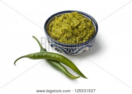 Bowl with green Moroccan harissa and fresh green chili peppers on white background