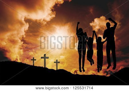Cheerful family jumping against cross religion symbol shape over sunset sky