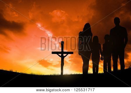 Cheerful family holding hands against cross religion symbol shape over sunset sky