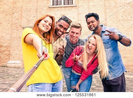 Multiracial group of friends taking selfie using mobile phone on self stick - Mixed race young tourists having fun doing photo in old city center - Concept of youth joyful moment Focus on left woman