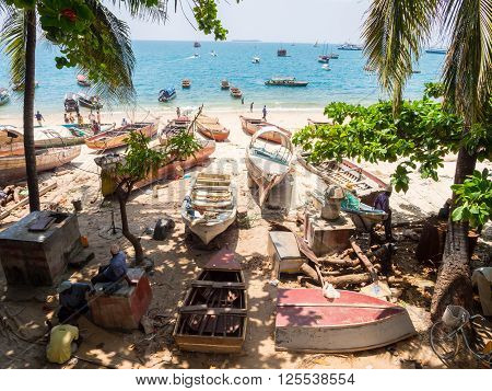 STONE TOWN ZANZIBAR - MARCH 28 2016: Local people with their boats on the seashore in Stone Town Zanzibar.