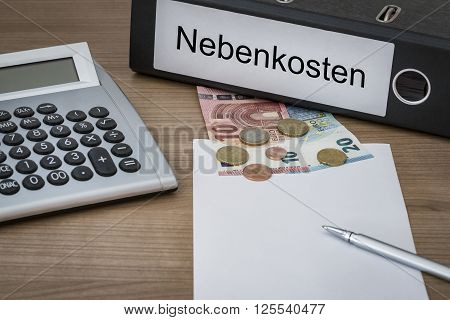 Nebenkosten (german aditional costs) written on a binder on a desk with euro money calculator blank sheet and pen poster