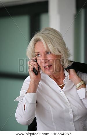 Portrait of a senior woman in suit on phone